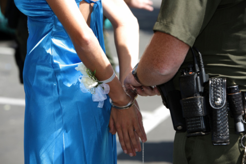Young woman in prom dress being arrested